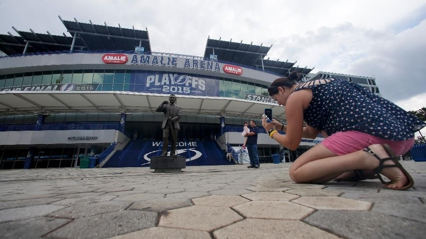 Tina Ward takes a picture of a statue of Phil Esposito, co-founder the Tampa Bay Lightning, outside Amalie Arena, Friday, June 5, 2015, in Tampa, Fla. While Sun Belt NHL teams from Phoenix to Miami struggle to maintain revenue and relevance in their communities, the Tampa Bay Lightning are thriving. The franchise's second trip to the Stanley Cup Final is the highlight of a revival under owner Jeff Vinik as the organization builds a vibrant hockey town in a warm-weather climate. Game 2 is scheduled for Saturday night against the Chicago Blackhawks. (AP Photo/Chris Carlson)