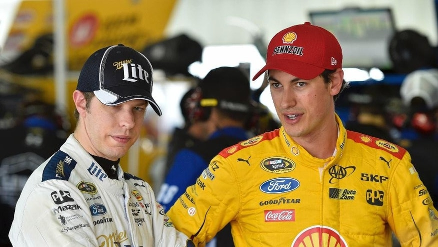 Brad Keselowski, left, stands with Joey Logano in the garage area at Pocono Raceway during practice for Sunday's NASCAR Sprint Cup Series auto race in Long Pond, Pa., Friday, June 5, 2015. (AP Photo/Derik Hamilton)