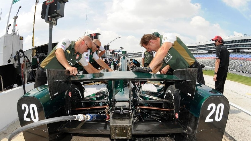 Crew members work on the car of Ed Carpenter (20) during a practice session for an IndyCar auto race at Texas Motor Speedway, Friday, June 5, 2015, in Fort Worth, Texas. IndyCar is mandating the use of closure panels on the rear wheel guards for the remaining three super speedway races. The decision is in response to three cars going airborne during preparation for the Indianapolis 500. (AP Photo/Larry Papke)