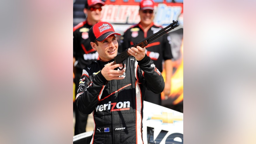 Will Power (1) of Australia poses with a rifle awarded to him after earning the pole position after qualifying for the Firestone 600 IndyCar auto race at Texas Motor Speedway Friday, June 5, 2015, in Fort Worth, Texas. The race is scheduled to run Saturday night. (AP Photo/Ralph Lauer)