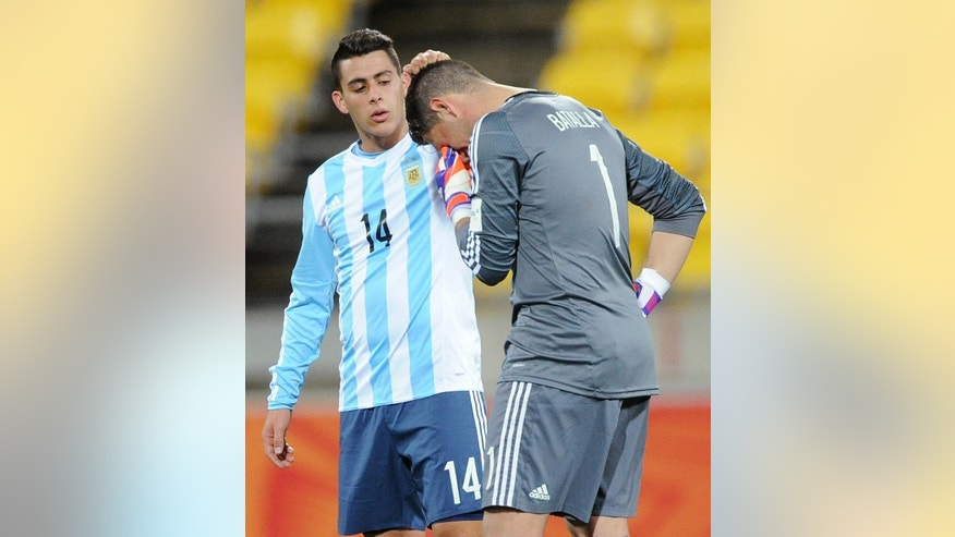 Argentina's Cristian Pavon, left, puts his hand on the head of his goalkeeper Augusto Batalla following their draw against Austria in their U20 soccer World Cup match in Wellington, New Zealand, Friday, June 5, 2015. (AP Photo/Ross Setford)