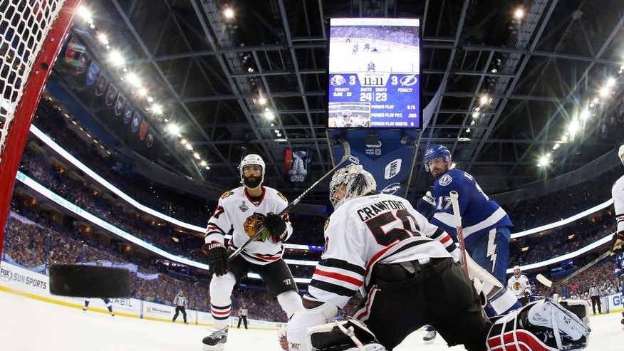 Chicago Blackhawks goalie Corey Crawford watches as Tampa Bay Lightning defenseman Jason Garrison's goal flies by during the third period in Game 2 of the NHL hockey Stanley Cup Final on Saturday, June 6, 2015, in Tampa Fla. (Bruce Bennett/Pool Photo via AP)