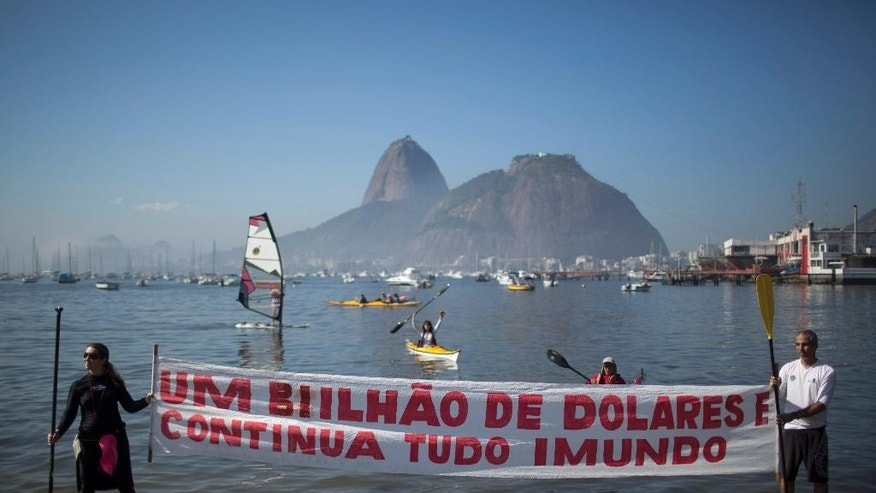 "Protesters hold a banner with a message that reads in Portuguese; ""One billion dollars and it's still disgusting"" during a demonstration on Botafogo Beach, in the Guanabara Bay in Rio de Janeiro, Brazil, Saturday, June 6, 2015, near where Olympic sailing events are to be held. Activists staged a demonstration on a sewage- and trash-filled strewn Rio de Janeiro beach to protest authorities' failure to make good on promises to clean up the Olympic city's filthy waterways ahead of the 2016 games. (AP Photo/Felipe Dana)"
