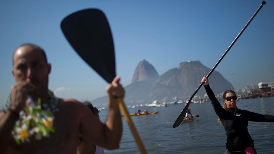 Protesters hold up paddles and whistle during a demonstration on Botafogo Beach, in the Guanabara Bay in Rio de Janeiro, Brazil, Saturday, June 6, 2015, near where Olympic sailing events are to be held. Activists staged a demonstration on the sewage- and trash-filled strewn Rio de Janeiro beach to protest authorities' failure to make good on promises to clean up the Olympic city's filthy waterways ahead of the 2016 games. (AP Photo/Felipe Dana)