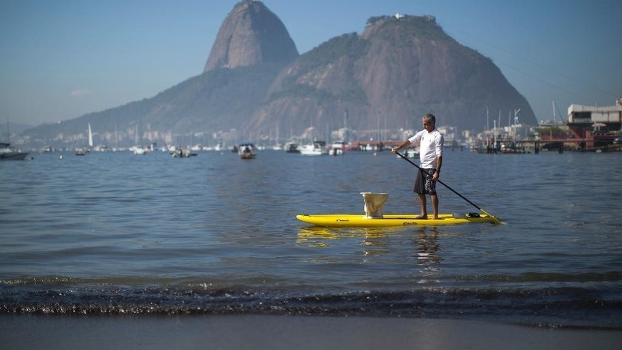 A protester paddles with a toilet atop his board during a demonstration on Botafogo Beach, in the Guanabara Bay in Rio de Janeiro, Brazil, Saturday, June 6, 2015, near where Olympic sailing events are to be held. Activists staged a demonstration on the sewage- and trash-filled strewn Rio de Janeiro beach to protest authorities' failure to make good on promises to clean up the Olympic city's filthy waterways ahead of the 2016 games. (AP Photo/Felipe Dana)
