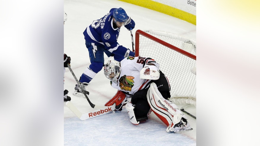 Tampa Bay Lightning center Tyler Johnson, top, scores past Chicago Blackhawks goalie Corey Crawford during the second period in Game 2 of the NHL hockey Stanley Cup Final on Saturday, June 6, 2015, in Tampa Fla. (AP Photo/John Raoux)