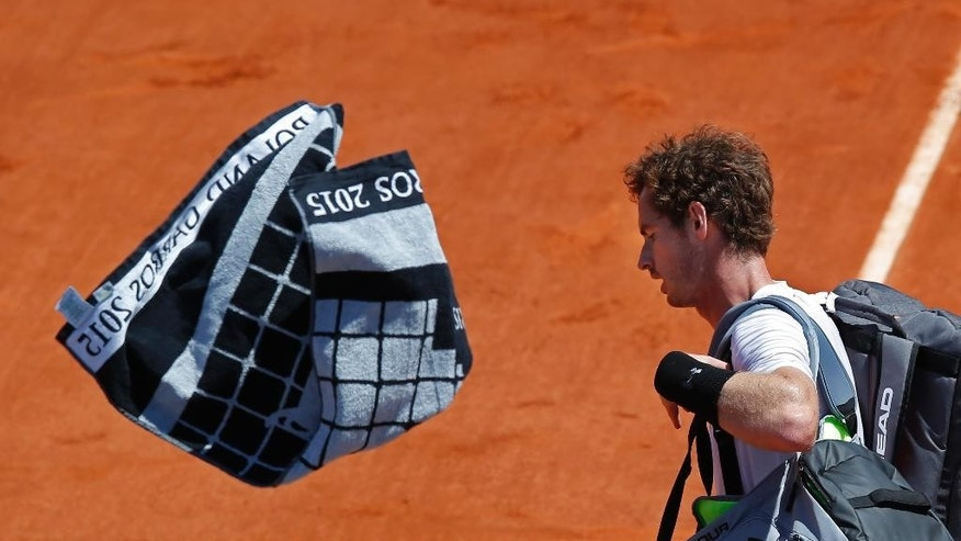 Britain's Andy Murray throws his towel as he leaves center court while Serbia's Novak Djokovic celebrates winning the semifinal match of the French Open tennis tournament in five sets 6-3, 6-3, 5-7, 5-7, 6-1, at the Roland Garros stadium, in Paris, France, Saturday, June 6, 2015. (AP Photo/Michel Euler)