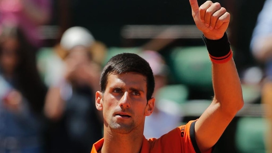 Serbia's Novak Djokovic thumbs up after defeating Britain's Andy Murray during their semifinal match of the French Open tennis tournament at the Roland Garros stadium, Saturday, June 6, 2015 in Paris.  (AP Photo/Christophe Ena)