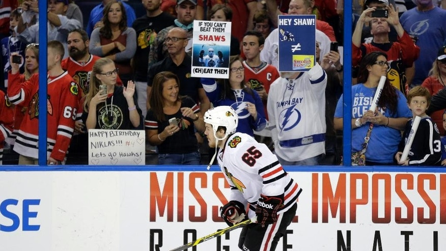 A fans hold up a signs regarding the alleged bite of Tampa Bay Lightning defenseman Victor Hedman by Chicago Blackhawks center Andrew Shaw in Game 1, before Game 2 of the NHL hockey Stanley Cup Final in Tampa, Fla., Saturday, June 6, 2015.  (AP Photo/Chris O'Meara)(AP Photo/Chris O'Meara)