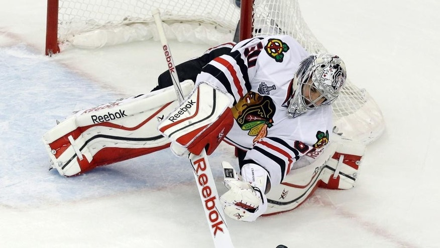 Chicago Blackhawks goalie Corey Crawford makes a save against the Tampa Bay Lightning during the second period in Game 2 of the NHL hockey Stanley Cup Final on Saturday, June 6, 2015, in Tampa Fla. (AP Photo/John Raoux)