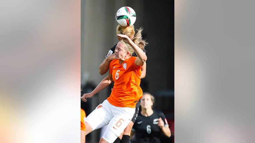 Netherlands' Lieke Martens (11) heads the ball as New Zealand's Ria Percival (2) defends during a FIFA Women's World Cup soccer match in Edmonton, Alberta Saturday,  June 6, 2015. (Jeff McIntosh/The Canadian Press via AP)