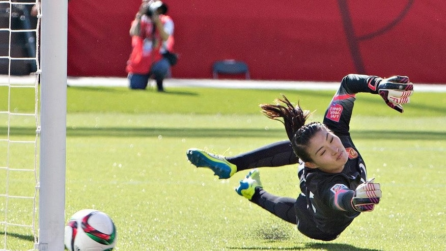 China goalkeeper Wang Fei lets in a penalty shot by Canada's Christine Sinclair during a FIFA Women's World Cup soccer match in Edmonton, Alberta, Saturday, June 6, 2015.  (Jason Franson/The Canadian Press via AP) MANDATORY CREDIT
