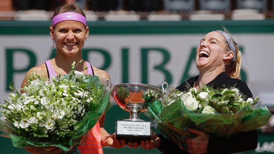 Bethanie Mattek-Sands of the U.S., right, and   Lucie Safarova of the Czech Republic, left, hold the trophy after winning the women's doubles final of the French Open tennis tournament in three sets, 3-6, 6-4, 6-2, against Casey Dellacqua of Australia and Yaroslava Shvedova of Kazakhstan at the Roland Garros stadium, in Paris, France, Sunday, June 7, 2015. (AP Photo/Thibault Camus)