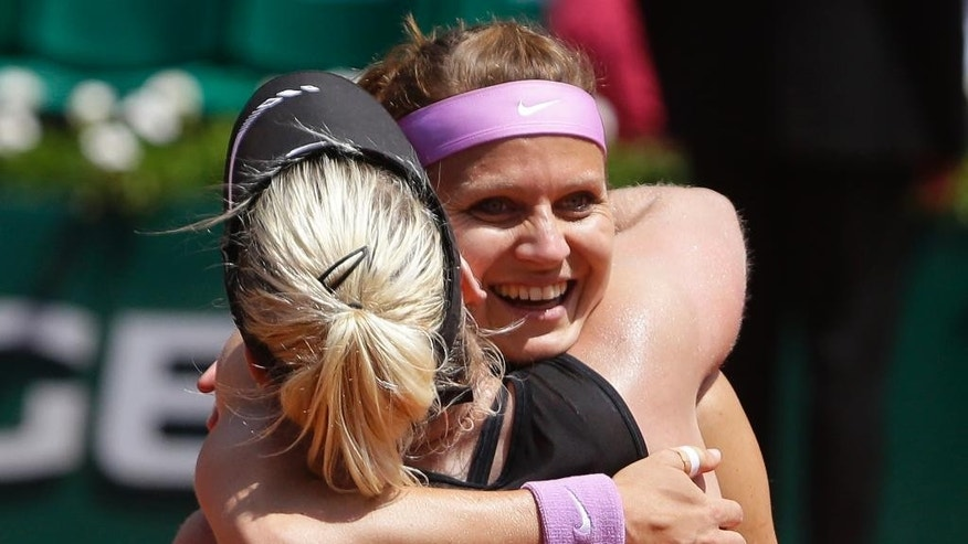 Bethanie Mattek-Sands of the U.S. hugs Lucie Safarova of the Czech Republic, right,   after winning the women's doubles final of the French Open tennis tournament in three sets, 3-6, 6-4, 6-2, against Casey Dellacqua of Australia and Yaroslava Shvedova of Kazakhstan at the Roland Garros stadium, in Paris, France, Sunday, June 7, 2015. (AP Photo/Thibault Camus)