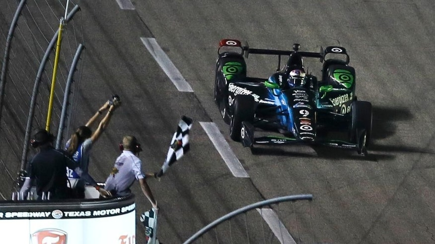 Scott Dixon (9) of New Zealand takes the checkered flag to win the Firestone 600 IndyCar auto race at Texas Motor Speedway Saturday, June 6, 2015, in Fort Worth, Texas. (AP Photo/Ralph Lauer)