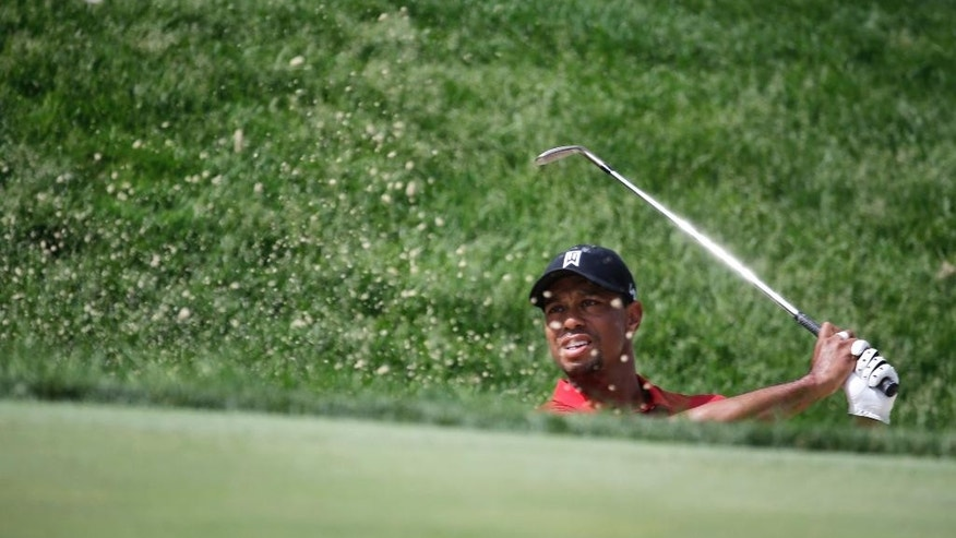 Tiger Woods hits out of the bunker on the 17th hole during the final round of the Memorial golf tournament Sunday, June 7, 2015, in Dublin, Ohio. (AP Photo/Darron Cummings)