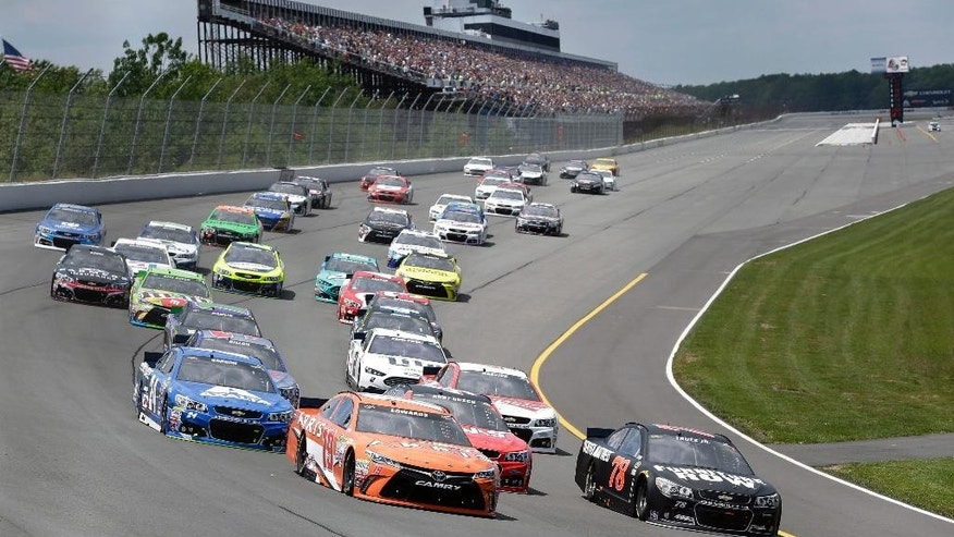 Carl Edwards (19) and Martin Truex Jr. (78) lead the pack into Turn 1 as pole-sitter Kurt Busch (41), center, is squeezed back at the start of a NASCAR Sprint Cup Series auto race at Pocono Raceway in Long Pond, Pa., Sunday, June 7, 2015. (AP Photo/Mel Evans)