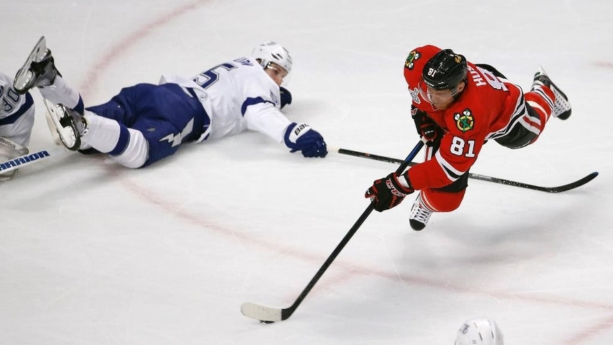 Chicago Blackhawks' Marian Hossa, of Slovakia, gets off a shot as Tampa Bay Lightning's Braydon Coburn, left, watches during the first period in Game 3 of the NHL hockey Stanley Cup Final on Monday, June 8, 2015, in Chicago. (AP Photo/Charles Rex Arbogast)