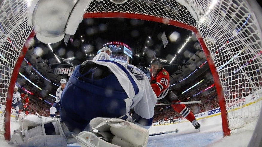 Tampa Bay Lightning goalie Ben Bishop, left, falls after being knocked to the ice by Chicago Blackhawks' Brandon Saad, right, during the second period in Game 3 of the NHL hockey Stanley Cup Final on Monday, June 8, 2015, in Chicago. (Bruce Bennett/Pool Photo via AP)