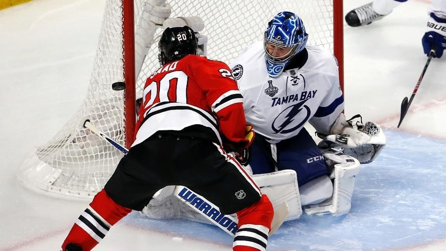 Chicago Blackhawks' Brandon Saad, right, shoots wide of Tampa Bay Lightning goalie Ben Bishop during the third period in Game 3 of the NHL hockey Stanley Cup Final on Monday, June 8, 2015, in Chicago. (AP Photo/Charles Rex Arbogast)