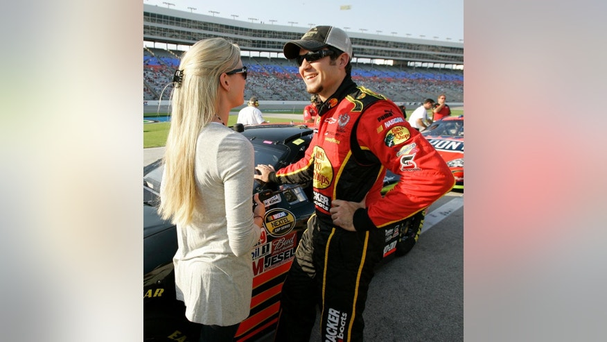 FILE - In this Nov. 2, 2007, file photo, NASCAR Nextel driver Martin Truex Jr. smiles as he chats with his girlfriend Sherry Pollex, left, along pit road during qualifying for the Dickies 500 auto race at Texas Motor Speedway in Fort Worth, Texas. (AP Photo/Tony Gutierrez, File)