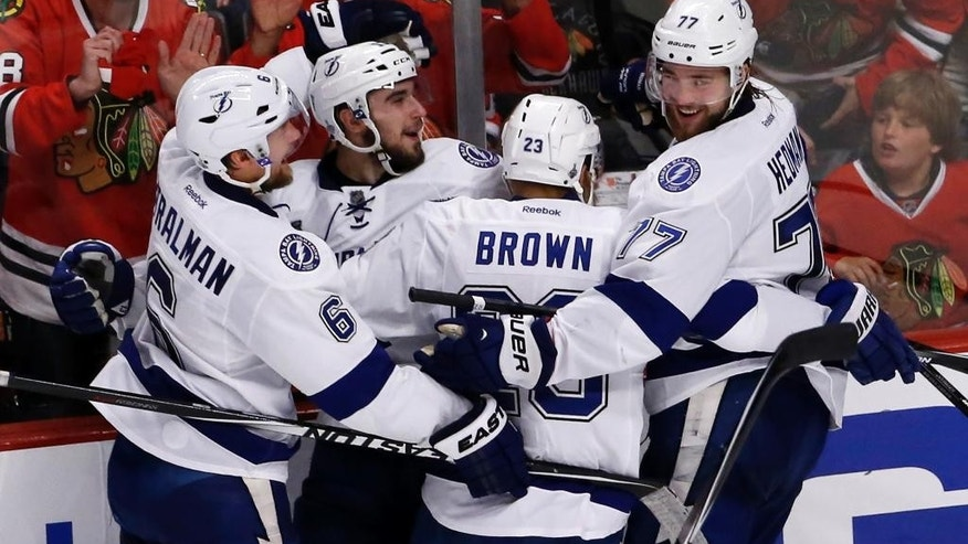 Tampa Bay Lightning's Cedric Paquette, second from left, is congratulated teammates Anton Stralman, left, J.T. Brown, and Victor Hedman, right, after scoring during the third period in Game 3 of the NHL hockey Stanley Cup Final against the Chicago Blackhawks on Monday, June 8, 2015, in Chicago. (AP Photo/Charles Rex Arbogast)