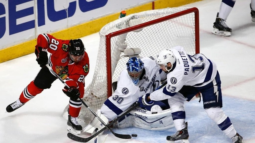 Chicago Blackhawks' Brandon Saad, left, reaches for a puck as Tampa Bay Lightning goalie Ben Bishop and Cedric Paquette, right, defend during the third period in Game 3 of the NHL hockey Stanley Cup Final on Monday, June 8, 2015, in Chicago. (AP Photo/Charles Rex Arbogast)