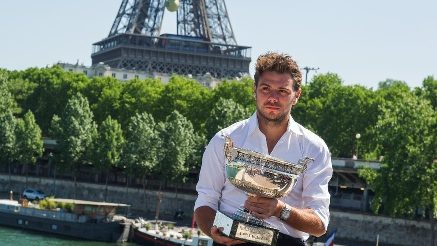 French Open Men's Singles champion Stan Wawrinka of Switzerland poses for a photo with his trophy in front of the Eiffel tower in Paris, France, Monday, June 8, 2015.  Wawrinka defeated Serbia's Novak Djokovic  in four sets, 4-6, 6-4, 6-3, 6-4, in the men's final of the French Open tennis tournament, at Roland Garros stadium in Paris. (AP Photo/Kamil Zihnioglu)