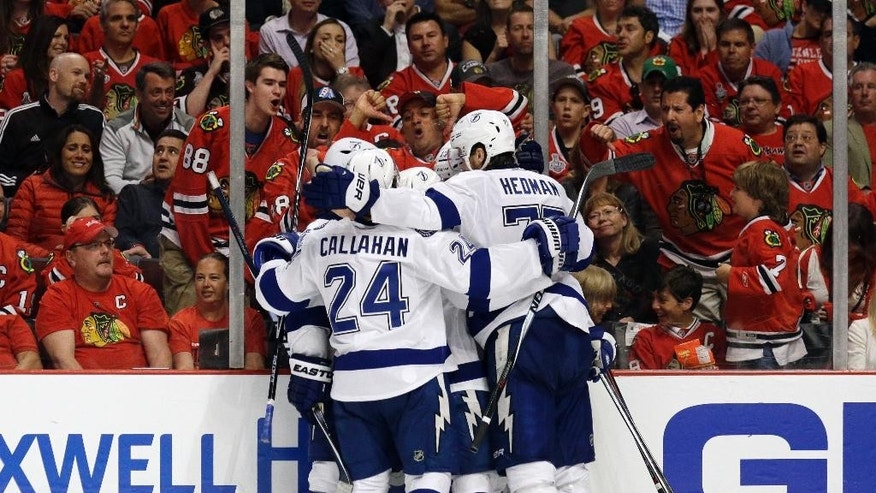 Teammates congratulate Tampa Bay Lightning's Cedric Paquette on his goal during the third period in Game 3 of the NHL hockey Stanley Cup Final against the Chicago Blackhawks on Monday, June 8, 2015, in Chicago. The Lightning won 3-2. (AP Photo/Nam Y. Huh)
