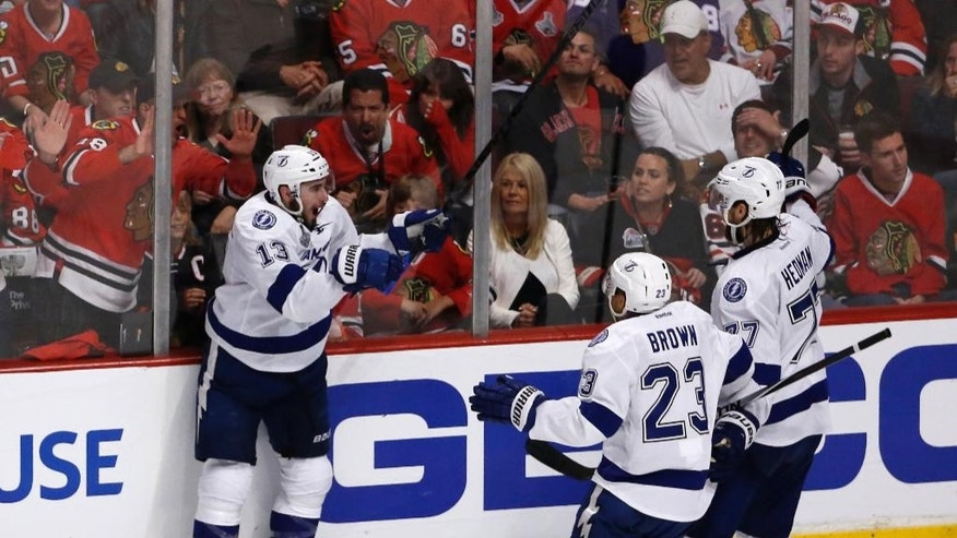 Tampa Bay Lightning's Cedric Paquette (13) is congratulated by J.T. Brown (23) and Victor Hedman (77) after scoring during the third period in Game 3 of the NHL hockey Stanley Cup Final against the Chicago Blackhawks on Monday, June 8, 2015, in Chicago. (AP Photo/Charles Rex Arbogast)