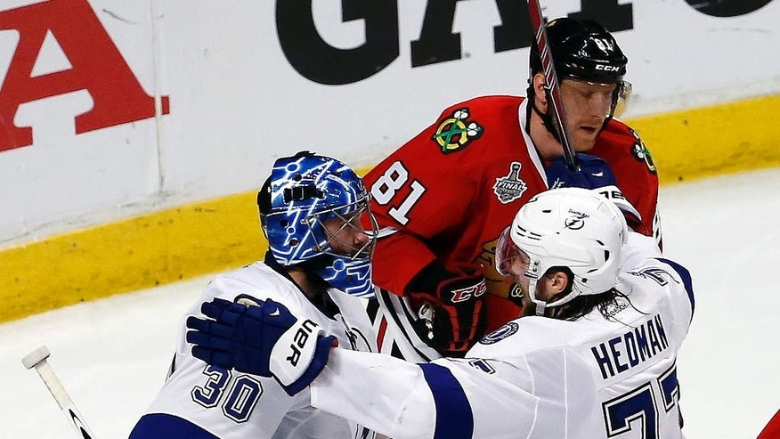 Tampa Bay Lightning goalie Ben Bishop (30) and Victor Hedman (77) celebrate as Chicago Blackhawks' Marian Hossa (81) skates past following the Lightning's 3-2 victory in Game 3 of the NHL hockey Stanley Cup Final on Monday, June 8, 2015, in Chicago. (AP Photo/Charles Rex Arbogast)