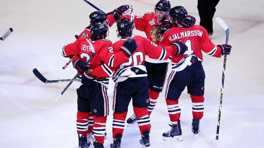 Teammates gather around Chicago Blackhawks' Brandon Saad (20) to celebrate his goal during the third period in Game 3 of the NHL hockey Stanley Cup Final against the Tampa Bay Lightning on Monday, June 8, 2015, in Chicago. (AP Photo/Charles Rex Arbogast)