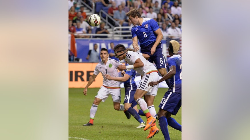 FILE - In this April 15, 2015, file photo, United States forward Jordan Morris (8) heads the ball at goal over Mexico's Carlos Salcedo (13) during the first half of an international friendly soccer match in San Antonio. Morris has Type 1 diabetes, so getting the symbol for his disease inked on his right forearm serves dual purposes: as medical identification if needed and also as a reminder to the Stanford star what he has endured to become a contributor for the U.S. men's national team at age 20. Not that he intended to ever do it. (AP Photo/Darren Abate, File)