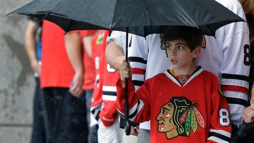 A young boy stands in the rain as he waits outside the United Center before the start of Game 4 of the NHL hockey Stanley Cup Final between the Chicago Blackhawks and the Tampa Bay Lightning Wednesday, June 10, 2015, in Chicago. (AP Photo/Nam Y. Huh)