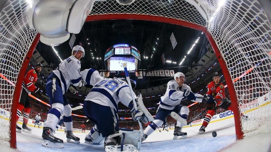 Chicago Blackhawks' Jonathan Toews, right, scores past, from left to right, Tampa Bay Lightning's Anton Stralman, of Sweden, goalie Andrei Vasilevskiy, and Ondrej Palat, of the Czech Republic, during the second period in Game 4 of the NHL hockey Stanley Cup Final on Wednesday, June 10, 2015, in Chicago. (Bruce Bennett/Pool Photo via AP)