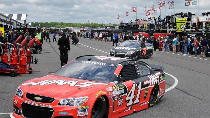 Kurt Busch (14) and Martin Truex Jr. (78) drive through the garage area at Pocono Raceway during practice for Sunday's NASCAR Sprint Cup Series auto race in Long Pond, Pa., Saturday, June 6, 2015. (AP Photo/Mel Evans)