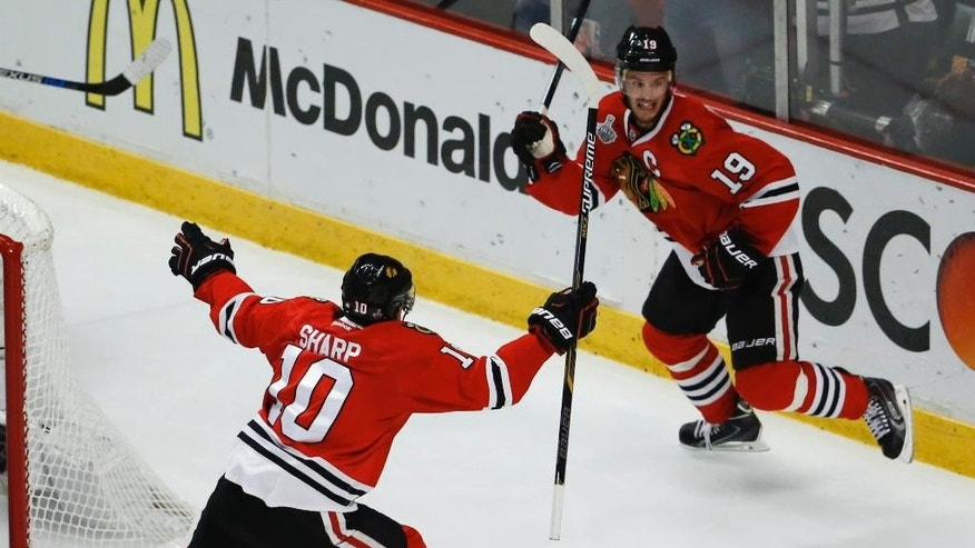 Chicago Blackhawks' Jonathan Toews, right, is congratulated by Patrick Sharp after scoring during the second period in Game 4 of the NHL hockey Stanley Cup Final against the Tampa Bay Lightning Wednesday, June 10, 2015, in Chicago. (AP Photo/Charles Rex Arbogast)