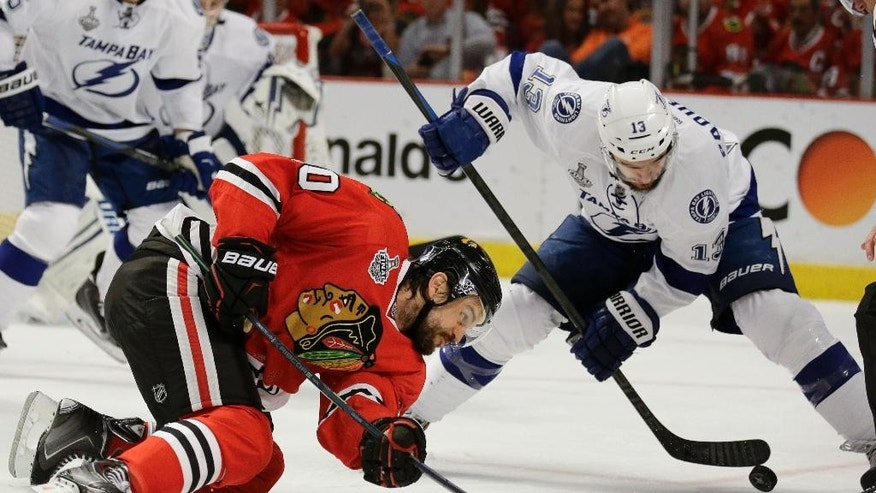 Chicago Blackhawks' Antoine Vermette, left, watches as Tampa Bay Lightning's Cedric Paquette handles the puck during the second period in Game 4 of the NHL hockey Stanley Cup Final Wednesday, June 10, 2015, in Chicago. (AP Photo/Nam Y. Huh)