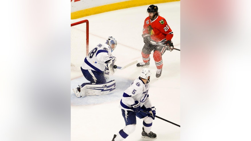 Tampa Bay Lightning goalie Andrei Vasilevskiy, left, deflects a puck as teammate Jason Garrison (5) and Chicago Blackhawks' Brandon Saad (20) watch during the third period in Game 4 of the NHL hockey Stanley Cup Final Wednesday, June 10, 2015, in Chicago. (AP Photo/Charles Rex Arbogast)