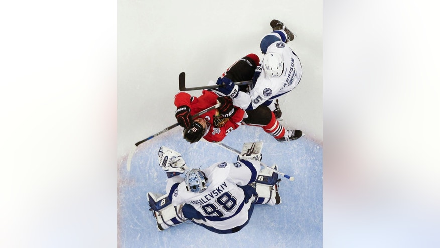Chicago Blackhawks' Jonathan Toews collides with Tampa Bay Lightning's Jason Garrison (5) as Lightning goalie Andrei Vasilevskiy, bottom, watches during the first period in Game 4 of the NHL hockey Stanley Cup Final Wednesday, June 10, 2015, in Chicago. The Blackhawks won 2-1 to tie the series 2-2. (AP Photo/Nam Y. Huh)