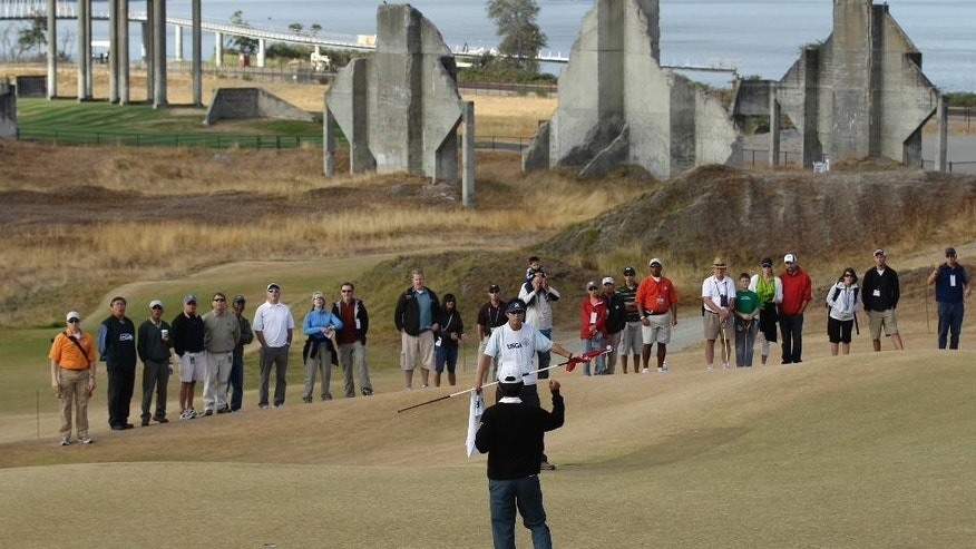 FILE - In this Aug. 28, 2010, file photo, David Chung reacts to sinking a putt during the U.S. Amateur golf tournament at Chambers Bay in University Place, Wash. In the background are concrete pilings and other remnants from the site's history a decade ago as an old sand and gravel pit. The course, which opened in 2007, will become the youngest golf course to host the U.S. Open since Hazeltine in 1970 when the tournament takes place later this month. (AP Photo/Ted S. Warren, file)