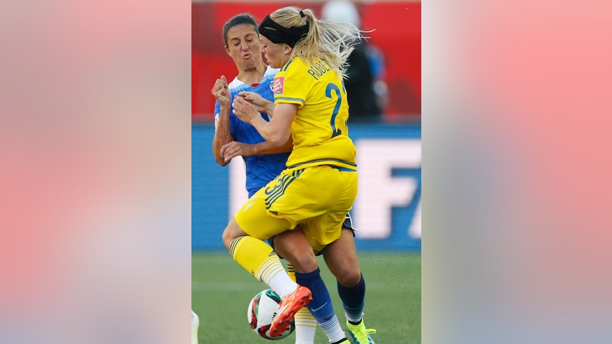 United States' Carli Lloyd (10) and Sweden's Elin Rubensson (23) collide during first-half FIFA Women's World Cup soccer game action in Winnipeg, Manitoba, Canada, Friday, June 12, 2015. (John Woods/The Canadian Press via AP) MANDATORY CREDIT