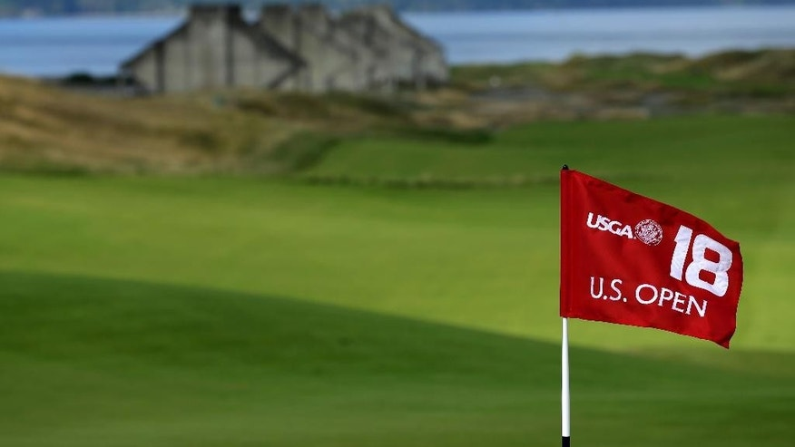 FILE - In this Sept. 30, 2014, file photo, the U.S. Open 18th hole flag is shown at Chambers Bay, the host course for the 2015 U.S. Open golf tournamen, in University Place, Wash. Chambers Bay will host the 115th U.S. Open golf tournament next week, but the course is a mystery to the majority of the players because it opened only eight years ago. (AP Photo/Ted S. Warren, file)