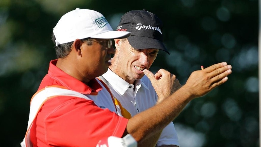 Steven Alker, right, of New Zealand, studies the eighth fairway with his caddie during the second round of the St. Jude Classic golf tournament Friday, June 12, 2015, in Memphis, Tenn. (AP Photo/Mark Humphrey)