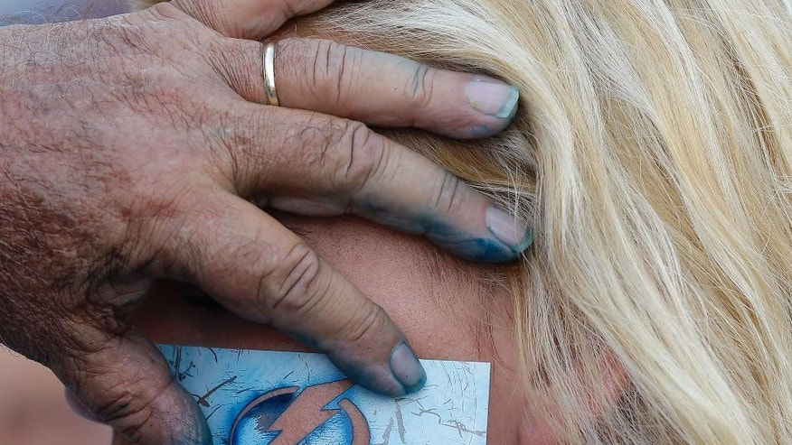 Bryanna White, of Tampa, Fla., has a lightning bolt stenciled on her face before the start of Game 5 of the NHL hockey Stanley Cup Final between the Chicago Blackhawks and the Tampa Bay Lightning, Saturday, June 13, 2015, in Tampa, Fla. (AP Photo/Chris O'Meara)