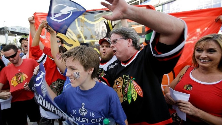 Tampa Bay Lightning and Chicago Blackhawks fans cheer for a television camera before the start of Game 5 of the NHL hockey Stanley Cup Final, Saturday, June 13, 2015, in Tampa, Fla. (AP Photo/John Raoux)