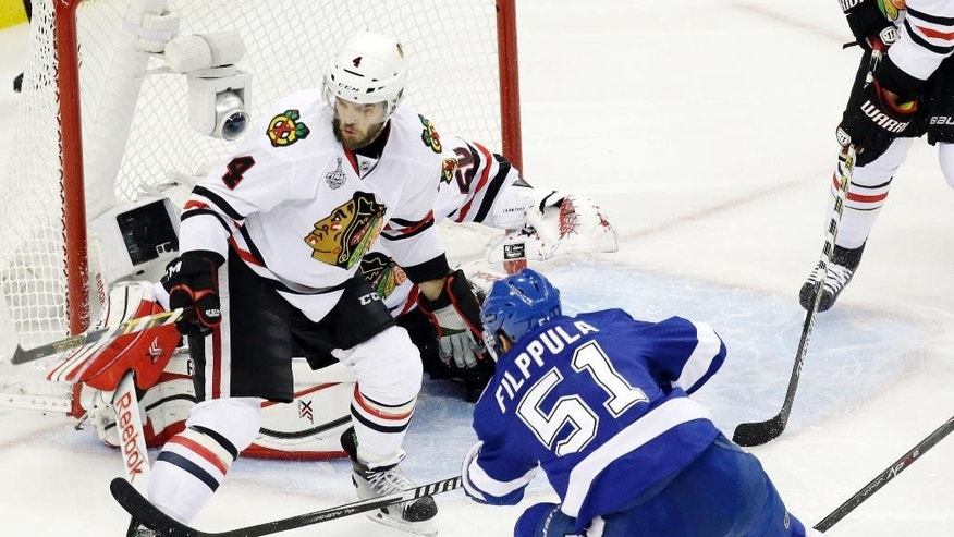 Chicago Blackhawks defenseman Niklas Hjalmarsson (4) kicks the puck away on a shot by Tampa Bay Lightning center Valtteri Filppula (51) during the first period of Game 5 of the NHL hockey Stanley Cup Final, Saturday, June 13, 2015, in Tampa, Fla. (AP Photo/John Raoux)