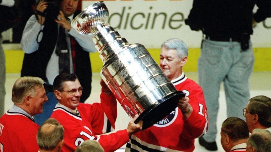 FILE - In this March 17, 1996, file photo, Stan Mikita (21) and Ed Lizenberger hoist the Stanley Cup during ceremonies to honor the Chicago Blackhawks' 1961 Stanley Cup Championship team before the Blackhawks NHL hockey game against the New York Islanders in Chicago. The family of Stan Mikita says the Chicago Blackhawks Hall of Famer no longer has memories of his exceptional career on the ice because of a progressive brain disorder.  (AP Photo/Tim Boyle, File)
