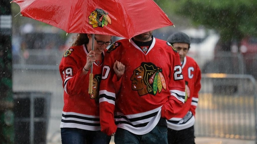 Chicago Blackhawks fans walk through the heavy rain as they arrive at United Center for Game 6 of the NHL hockey Stanley Cup Final between the Chicago Blackhawks and the Tampa Bay Lightning on Monday, June 15, 2015, in Chicago. (AP Photo/Nam Y. Huh)
