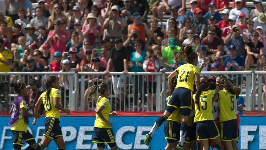 Colombia celebrates their 2-0 victory over France in a FIFA Women's World Cup soccer game in Moncton, New Brunswick, Canada, on Saturday, June 13, 2015. (Andrew Vaughan/The Canadian Press via AP) MANDATORY CREDIT